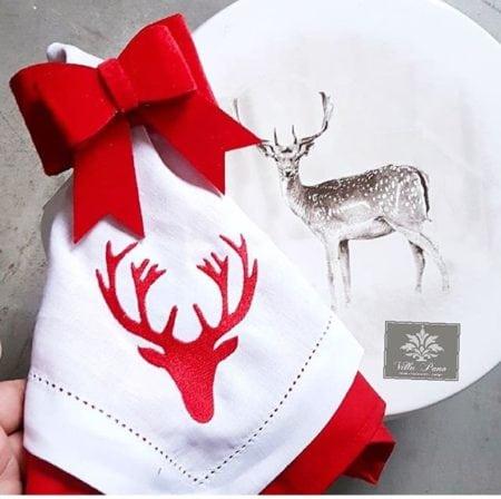 Guardanapo e prato com alce estampado para decorar a mesa de Natal.