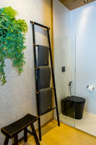 Escada decorativa usada como toalheiro no banheiro. Espaço na Casa Cor Rio.