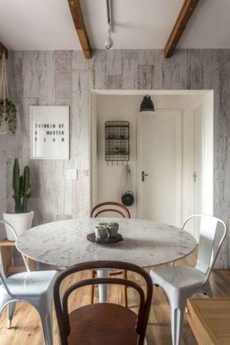 Decoração estilo escandinavo, com a parede revestida com lambri em madeira lavada.
