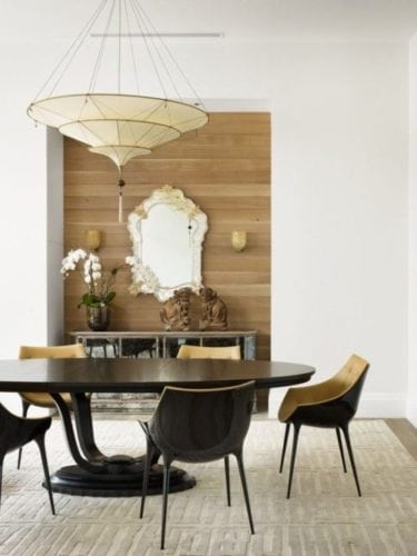 Sala de jantar, parede com nicho do piso ao teto, revestido com lambri em madeira no sentido horizontal para destacar o espelho veneziano.