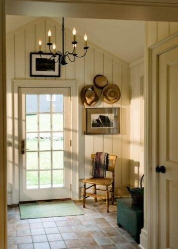 Hall de entrada de casa de campo, madeira revestindo as paredes.