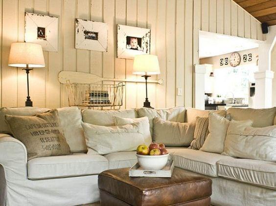 Sala de casa de praia, revestidas com lambri pintado de branco, do piso ao teto.