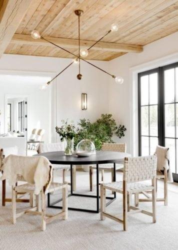 Sala de jantar com o teto revestido com lambri em madeira.