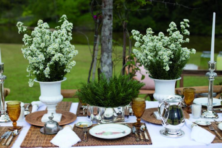 Inspirações para se criar mesas caprichadas. Mesa com arranjos de flor branca e decorada com peças em prata e rattan.