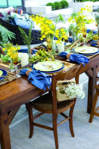 Mesa decorada com cachos de banana e na cadeira uma cestinha com flor .
