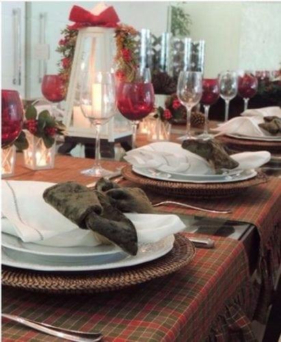 Mesa de Natal tradicional com toalha xadrez vermelha e verde e porta-guardanapo de veludo verde.