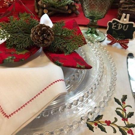 Mesa de Natal com porta-guardanapo de laço e com pinha enfeitando.