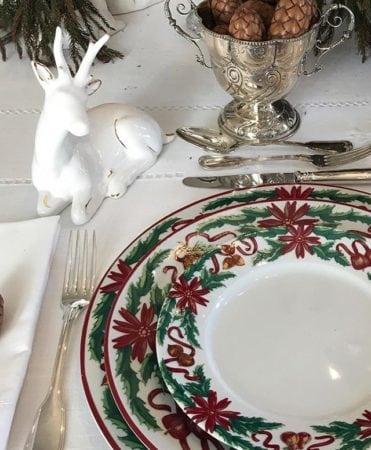 Mesa chic e tradicional de Natal. Toalha branca, faqueiro de prata e louça com tema natalino.