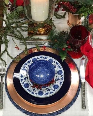 Mesa decorada de Natal com louça azul e vermelha.