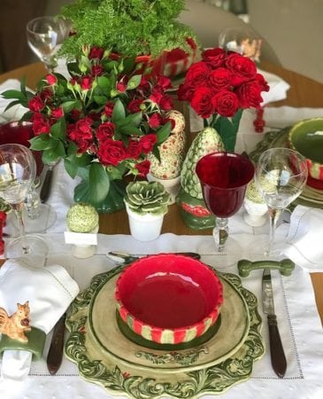 mesa decorada de Natal com pratos e potes em cerâmica vermelha e verde e arranjos com rosas vermelhas.