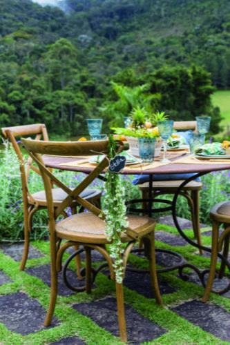 Inspirações para se criar mesas caprichadas. Detalhe da decoração da mesa, um ramo de flor pendurado na cadeira com plaquinha de marcador de lugar.