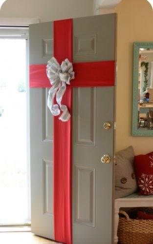 Porta de entrada decorada para o natal com laço vermelho.
