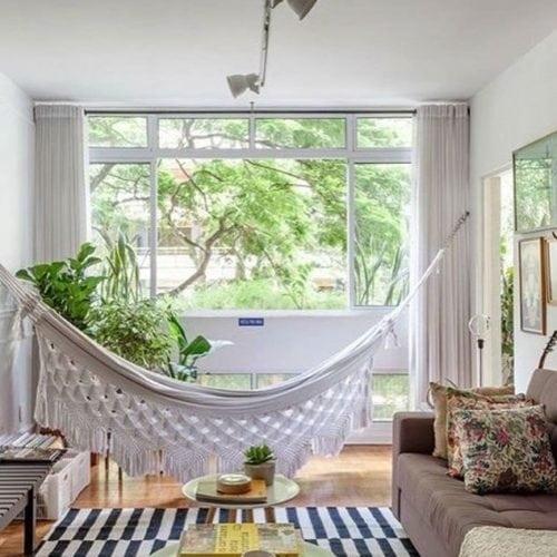 Rede na decoração, dentro de casa. A rede na cor crua, perto da janela e das plantas, é destaque na decoração da sala.