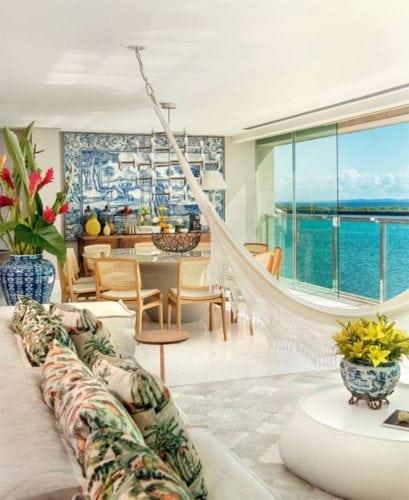 Sala do apartamento estilo praiano, com a rede pendurada dividindo ambientes.
