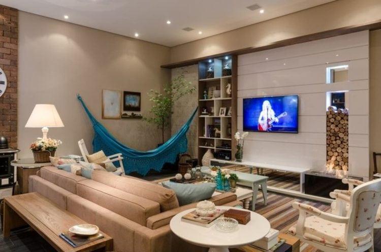 Rede turquesa pendurada na sala de tons neutros e estilo contemporâneo.