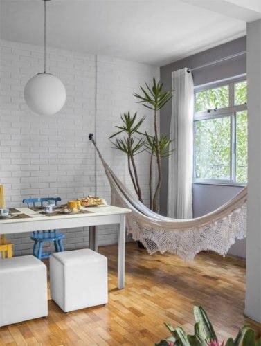 Redes na decoração, dentro de casa. Rede pendurada na parede de tijolinho branco ao lado da mesa de jantar.