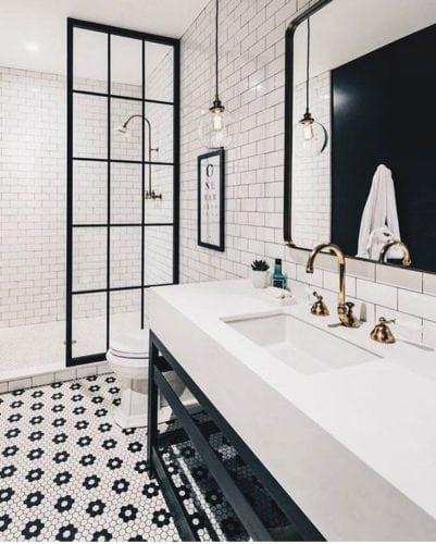 Banheiro decorado em preto e branco, bancada branca em cima do móvel preto.