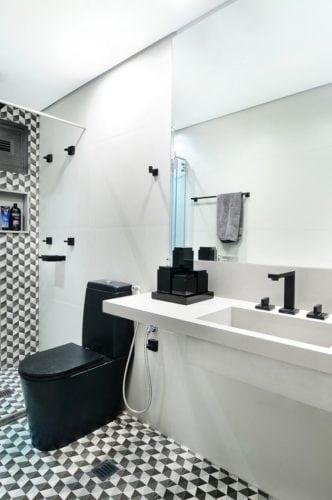 Banheiro decorado revestimento do box e piso em preto e branco, bancada em Corian branco e louças e metais em preto.