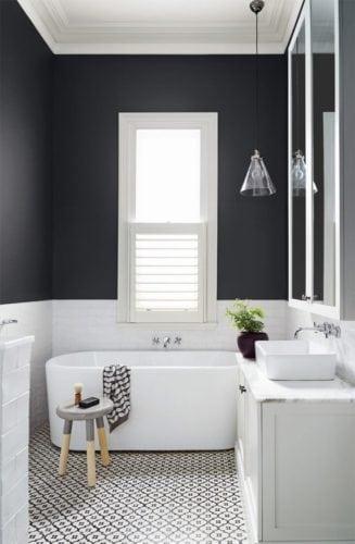 Banheiro preto e branco, meia parede pintado de preto fosco e piso em ladrilho hidráulico.