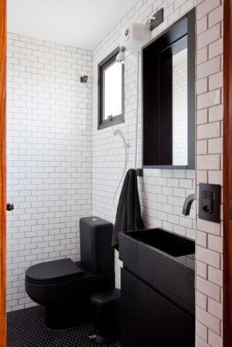 Banheiro com revestimento branco e louças e metais pretos.