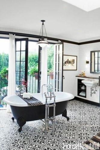 Destaque para a banheira preta e branca, no banheiro repleto de detalhes nessas cores.