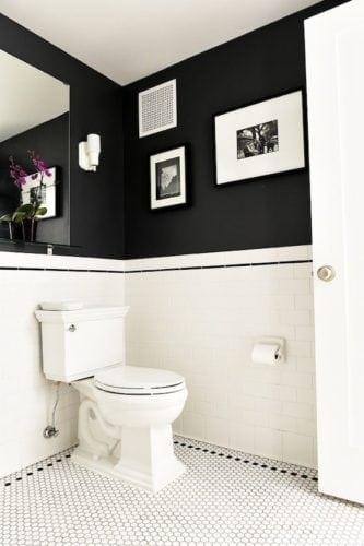 Banheiro em preto e branco, com meia parede pintada de preto fosco.