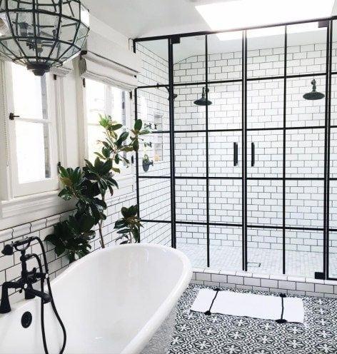 Banheiro decorado em preto e branco , com esquadria preta separando o box.