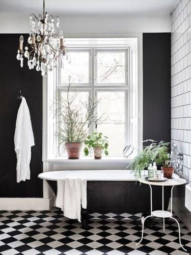 Banheiro decorado em preto e branco. Piso xadrex e paredes pintadas de preto fosco.