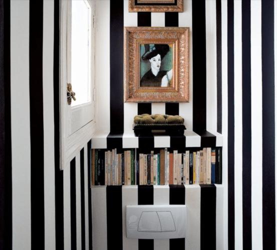 Lavabo decorado com papel de parede listrado de preto e branco.