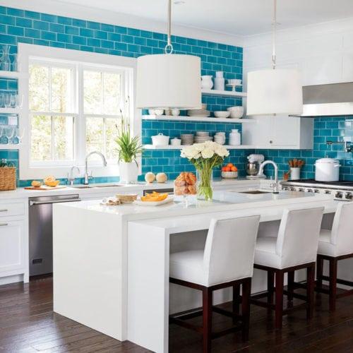 Ilha de cozinha com bancada de apoio , cuba e desnível para acomodar os assentos. Cozinha azul e branca.