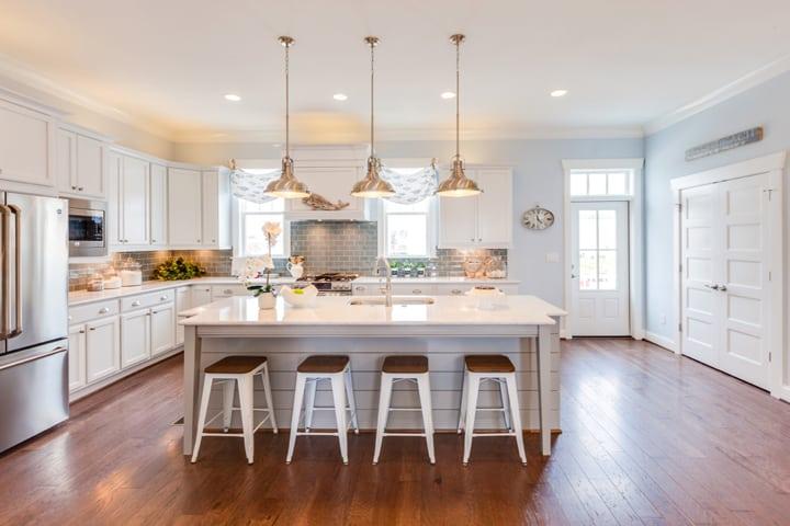 Ilha central na cozinha com um espaço generoso. Cozinha toda branca com piso em madeira.