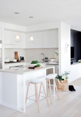 Ilha na cozinha como bancada de apoio e banquetas.