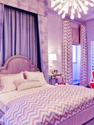 Quarto decorado com a cor lilás nas cortinas, na colcha e parede.