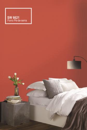 Tintas Sherwin-Williams, cor Forró Pé de Serra. Tom entre o vermelho a alaranjado. Parede do fundo da cama pintado nesse tom.