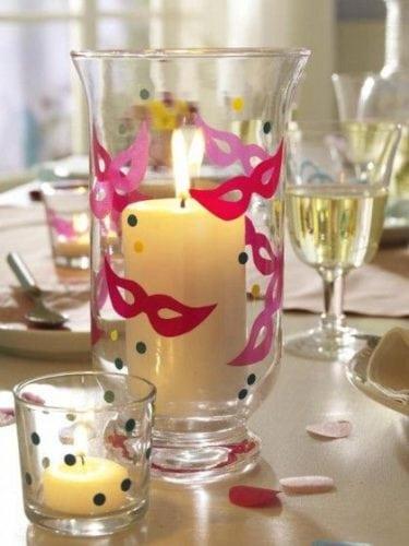 Ideias de decoração de Carnaval para festejar em casa. Centro de mesa com porta velas pintados com máscaras e confetes