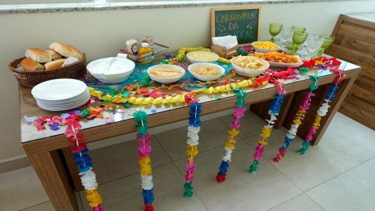Ideias de decoração de Carnaval para festejar em casa.buffet das comidas enfeitado com colar havaiano