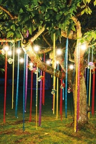 Ideias de decoração de Carnaval para festejar em casa.Arvore enfeitada com fitas coloridas e velas penduradas.