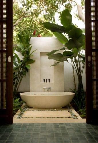 Banheiras fora dos banheiros. Banheira no jardim, ao lado de duas palmeiras.