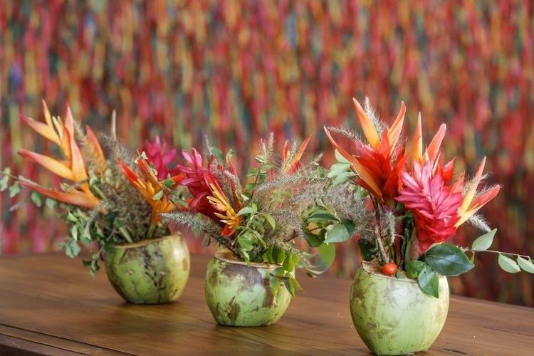 Coco verde usado com vaso para arranjo com flores tropicias