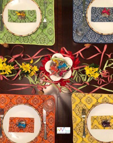 Mesa posta com 4 lugares, jogos americanos coloridos com tema de bandana e serpentina enfeitando o centro.