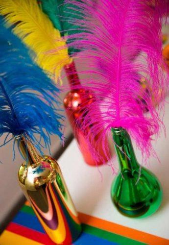 Vaso colorido com pluma dentro, enfeite de mesa