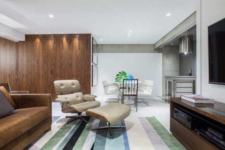 Ampla sala, com a cozinha aberta em frente a mesa de jantar. Sala decorada com painel em madeira na parede lateral.