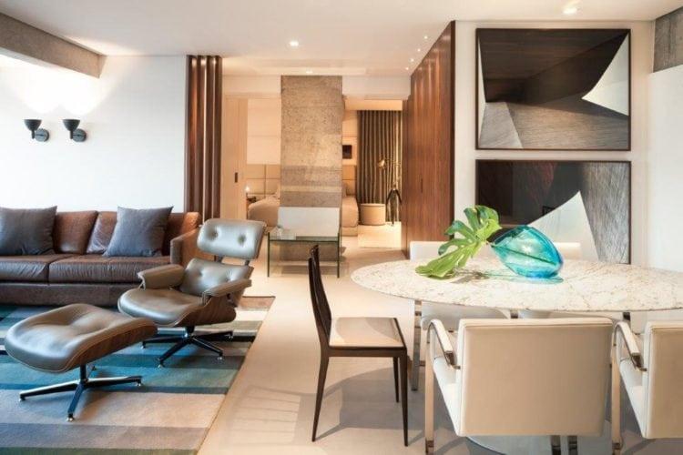 Amplo apartamento, com painel em madeira , mesa Saarinem e cadeira Charles Eames decorando.