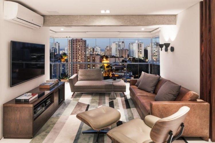 Sala de ampliada com a varanda envidraçada. Sofá de couro complementa a decoração para assistir a TV.