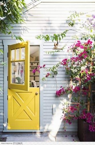 """A porta holandesa também é chamada de """"Dutch Door"""". Porta dividida ao meio, entrada do jardim pintada de cor amarela."""