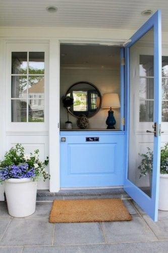"A porta holandesa também é chamada de ""Dutch Door"". Porta dividida ao meio, pintada de turquesa, na entrada da casa."