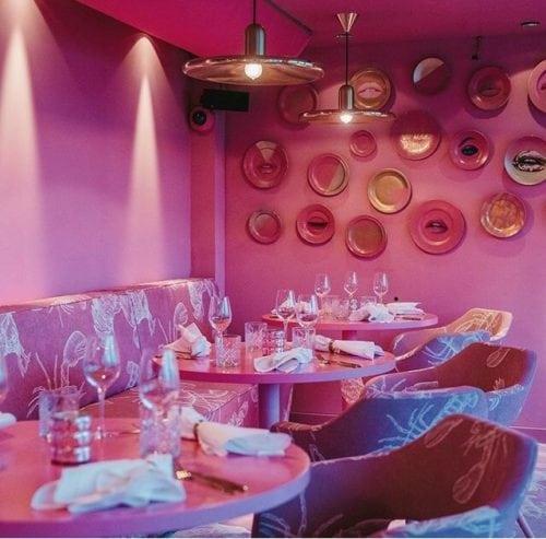 Restaurante MaMa kelly em Amsterdã decorado todo em Pink, inclusive parede e teto pintado dessa cor. Pratos rosa na parede decorando.