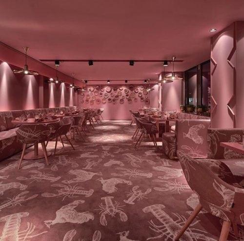 Restaurante MaMa kelly em Amsterdã decorado todo em Pink. Carpete, sofás e poltronas com o mesmo desenho. lagostas e frangos. Tudo com o fundo rosa.