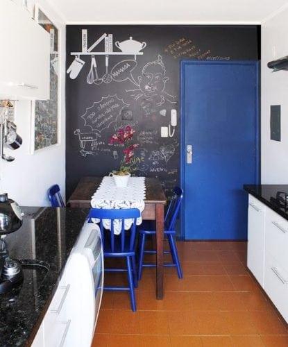 Inspirações para decorar usando lousa. Cozinha pequena, ganhou uma super bossa com a parede de fundo em lousa a porta azul contrastando.