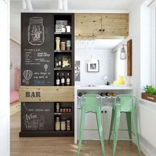 Inspirações para decorar usando lousa. Cozinha americana com a parede que dá para sala, com lousa para decorar.
